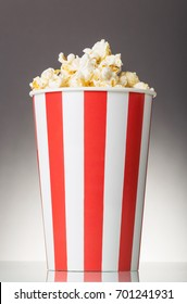 Full container with popcorn isolated on a gray background