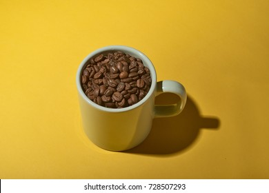 Full Cup of coffee beans on yellow  background