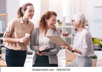 Full of delight at work. Diligent smiling positive businesswomen standing in the office and using the clipboard and the tablet while exchanging opinions