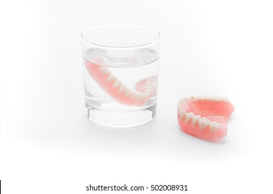Full Denture in glass of water on white background