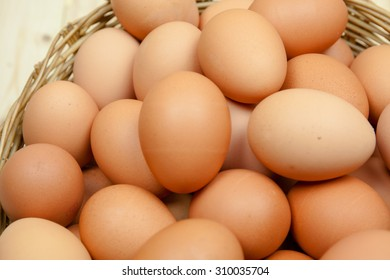Full of Eggs put in a wicker basket in wooden background from top view