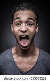 Full of emotions. Portrait of young excited African man looking at camera with mouth open while standing against black background