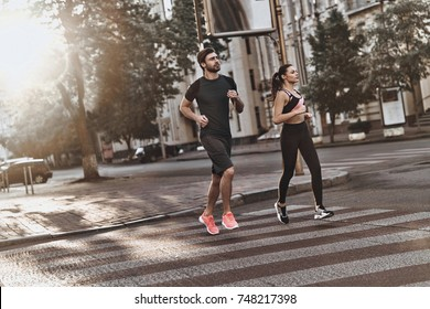 Full of energy. Full length of young couple in sport clothing running through the city street together