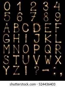 Full english alphabet and numbers set made from burning sparkles on black background. Shiny festive firework latin font.