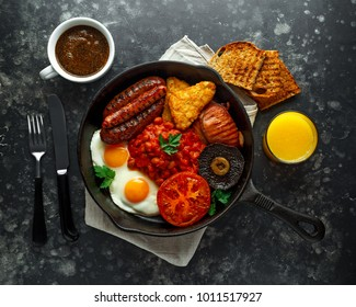 Full English breakfast with bacon, sausage, fried egg, baked beans, hash browns and mushrooms in rustic skillet, pan. cup coffe, orange juice