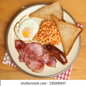 Full English breakfast with bacon, sausage, fried egg, baked beans and fried bread.