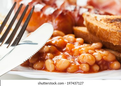Full English breakfast with bacon, sausage, fried egg, baked beans and tea