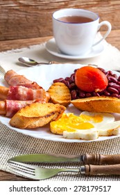 Full English breakfast with bacon, sausage, fried egg, baked beans and tea.