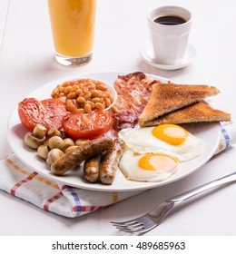full english breakfast with bacon, sausage, eggs, beans, mushrooms, on white tabel