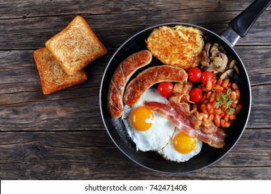 full english breakfast - bean, hash brown, fried eggs, bacon, roasted sausages, tomatoes, mushrooms on skillet on old dark wooden table with toasted bread, blank space left, view from above