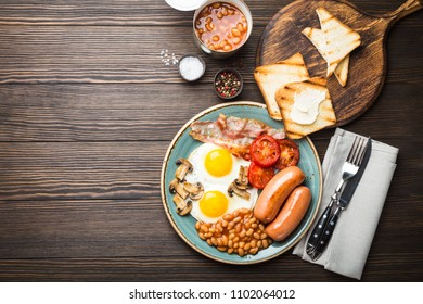 Full English breakfast with fried eggs, sausages, bacon, beans, mushrooms, tomatoes on a plate, bread toasts with butter. Traditional British meal, top view, rustic wooden background, space for text