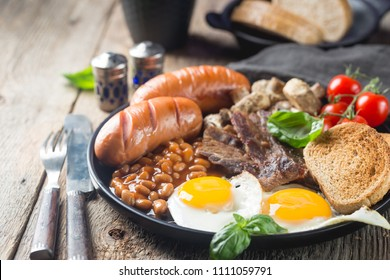 Full English breakfast with fried eggs, sausages, bacon, beans, toast and tomatoes on rustic wooden background