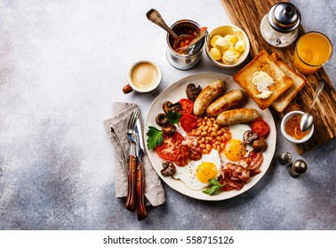 Full English breakfast with fried eggs, sausages, bacon, beans, toasts and coffee on copy space background