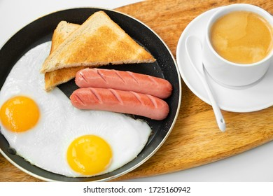Full English Breakfast including sausages, egg and bread in a skillet. Cup of coffee with milk. Top view.