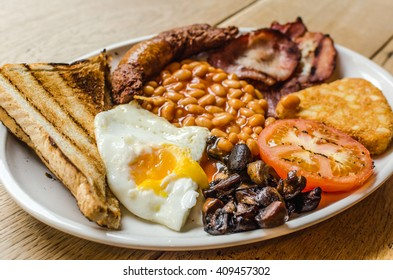Full English Breakfast including sausages, grilled tomatoes and mushrooms, egg, bacon, baked beans and bread.
