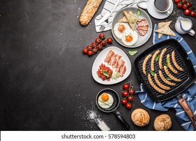 Full english breakfast on black chalkboard background. Layout with free text (copy) space captured from above (top view, flat lay). Coffee, fried eggs, baked beans, sausages, bread rolls and bacon.