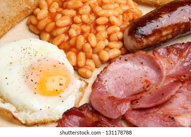 Full English cooked breakfast with bacon, sausage, fried egg and baked beans.