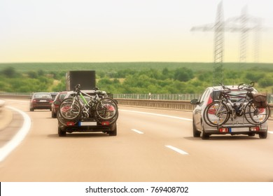 Full expressway in the holiday season with car carriers mounted on bicycles
