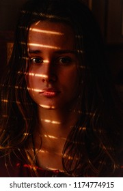 full face dark portrait of a young european girl with a striped shadow from the blinds, beautiful girl