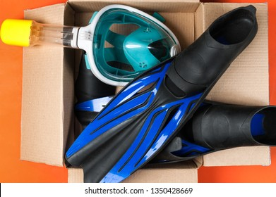 full face diving mask and flippers on the carton box