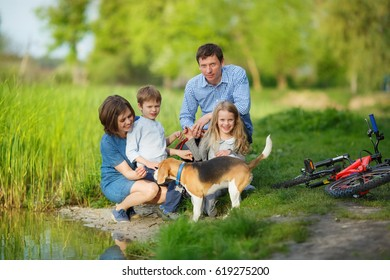 A full family is resting on the shore of a quiet lake. Mom, Dad, son, daughter and their dog sat by the water