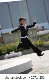 full figure with jump of a young adult businesswoman outdoors in a sunny day