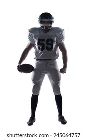 Full of forces and energy.  Full length of American football player holding ball and looking ay camera standing against white background