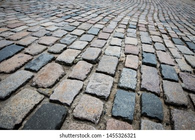A full frame background image of rows of cobblestones stretching into the distance on a cobble street with copy space