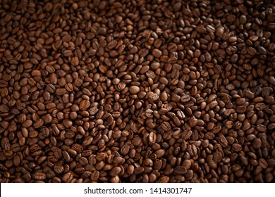 Full frame background texture of roasted coffee beans with side vignette in a close up overhead view