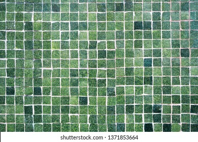 Full frame of broken pieces of ceramics tiled in mosaic on street wall in ceramic wall. Close up mosaic background in Spain.