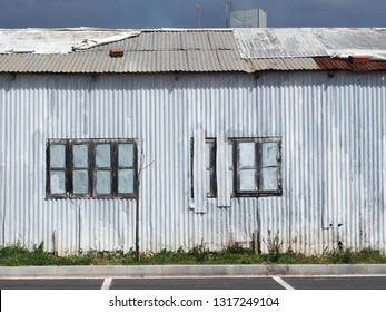 full frame close up of a shabby old dilapidated corrugated iron building with with closed painted over patched windows repaired rusting roof and white faded walls with a strip of overgrown grass