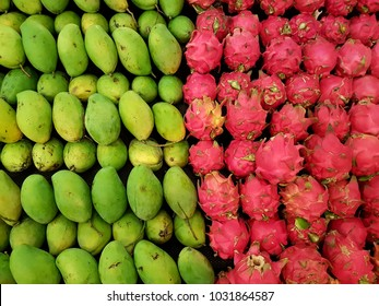 Full frame close-up shot of two different variety of fruits, green mangoes and pinkish red Dragon fruit