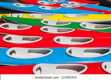 Full frame of colorful kayaks. Close up. Background. Red, blue, green and yellow.