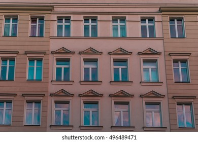 Full frame front view on three rows of stylish neo-classical type windows on apartment exterior