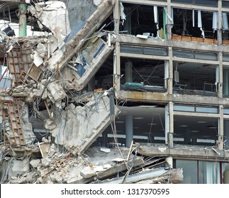 full frame image of a large destroyed collapsing building with exposed walls and smashed floors falling into rubble and tangled debris