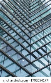 eine moderne Büroarchitektur in einem vollen Rahmen mit geometrisch eckigen Formen und Linien in blauen Glasfenstern