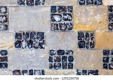 A full frame photograph of a flint and stone wall