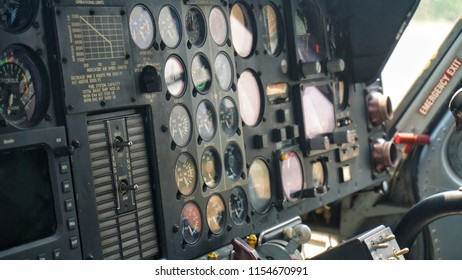 Full frame shot of Control panel in military helicopter cockpit, copter dashboard with displays, dials, buttons, switches, faders, knobs, other toggle items