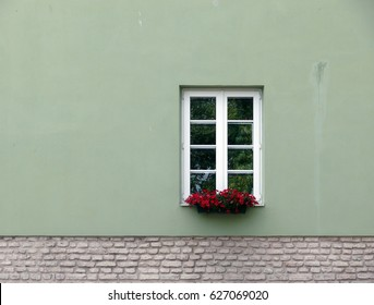 Full frame shot of exterior wall with window and flowers on sill in Vilnius, Lithuania.