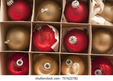 Full frame view of boxed festive red and gold Christmas baubles for decorating a seasonal holiday celebration party, overhead close up view