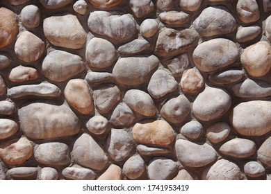 Full frame view of a section of a wall with large stones decoratively embedded in concrete