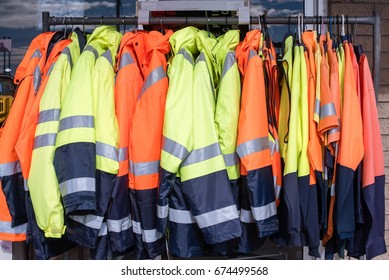 Full frame view of yellow and orange high visibility protective clothing on rack