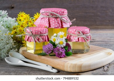 Full fresh liquid honey pots  with summer wild flowers on rustic wooden table