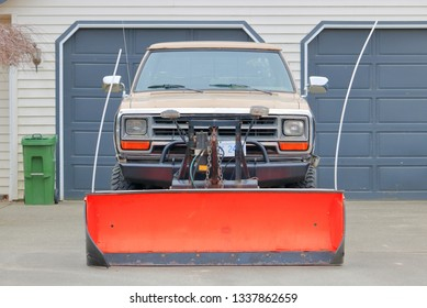 Full frontal view of a truck equipped with a large red blade that enables the private owner to use for removing snow.