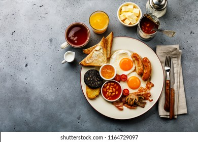 Full fry up English breakfast with fried eggs, sausages, bacon, black pudding, beans, toasts and tea on gray concrete background