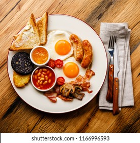 Full fry up English breakfast with fried eggs, sausages, bacon, black pudding, beans and toasts on wooden background