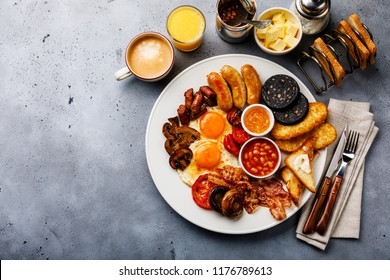 Full fry up English breakfast with fried eggs, sausages, bacon, black pudding, beans, toasts and coffee on gray concrete background