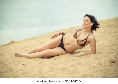 full girl posing on the beach in a bikini. plump woman sunbathing on the beach