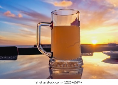 a full glass of beer against the evening sky photographed with pink violet clouds and setting sun in close-up. Reflection in the metal table.