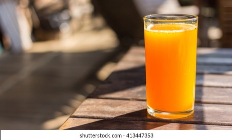 Full glass of orange juice close-up. Fresh orange juice on wooden table in out of focus unidentified restaurant in the morning in summer